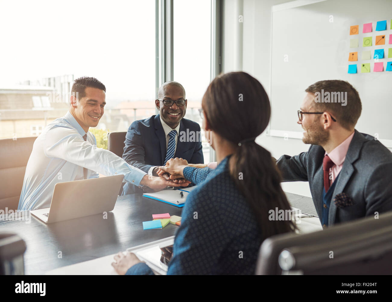 Successful multiracial business team working together affirm their commitment by linking hands across an office - Stock Image