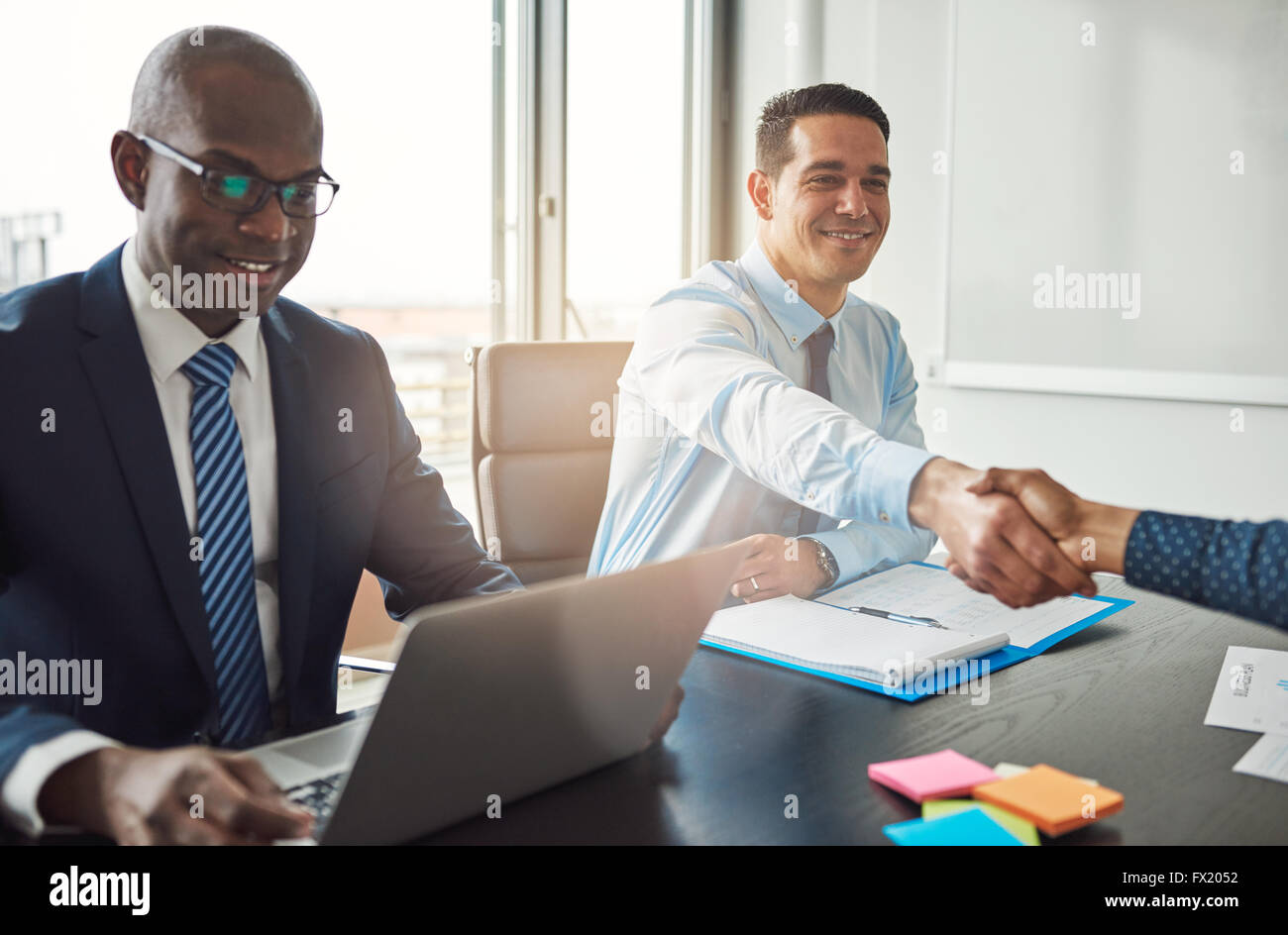 Smiling young Hispanic business man and woman shaking hands across a table in the office watched by a smiling African - Stock Image