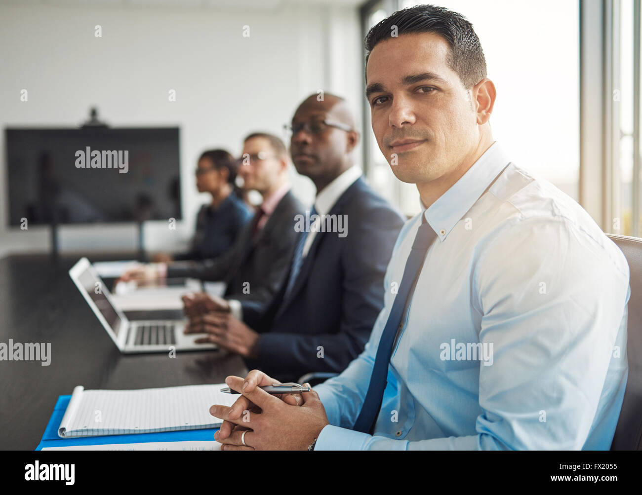 Young Hispanic businessman in a meeting with co-workers at the office sitting at a conference table turning to smile - Stock Image