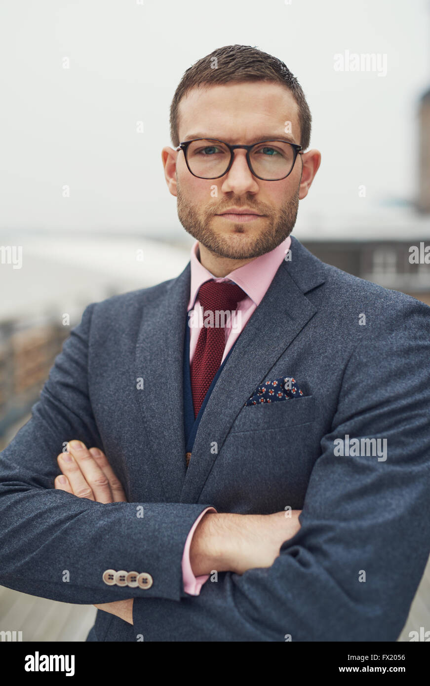 Serious determined young business man wearing glasses standing with folded arms looking at the camera with a pensive - Stock Image