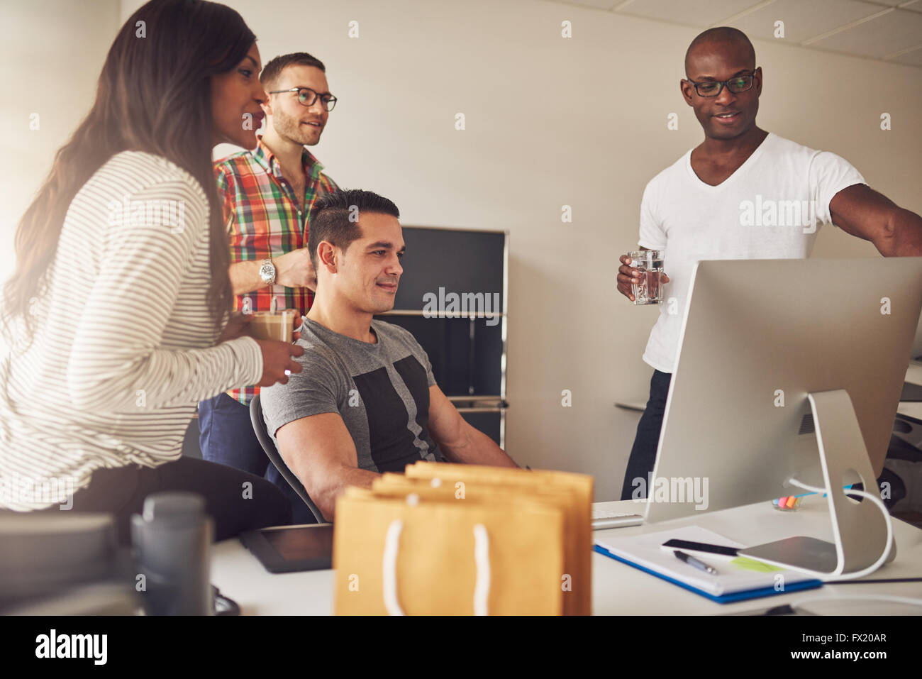 Diverse group of male and female adult entrepreneurs gathered together around large computer monitor on desk for - Stock Image