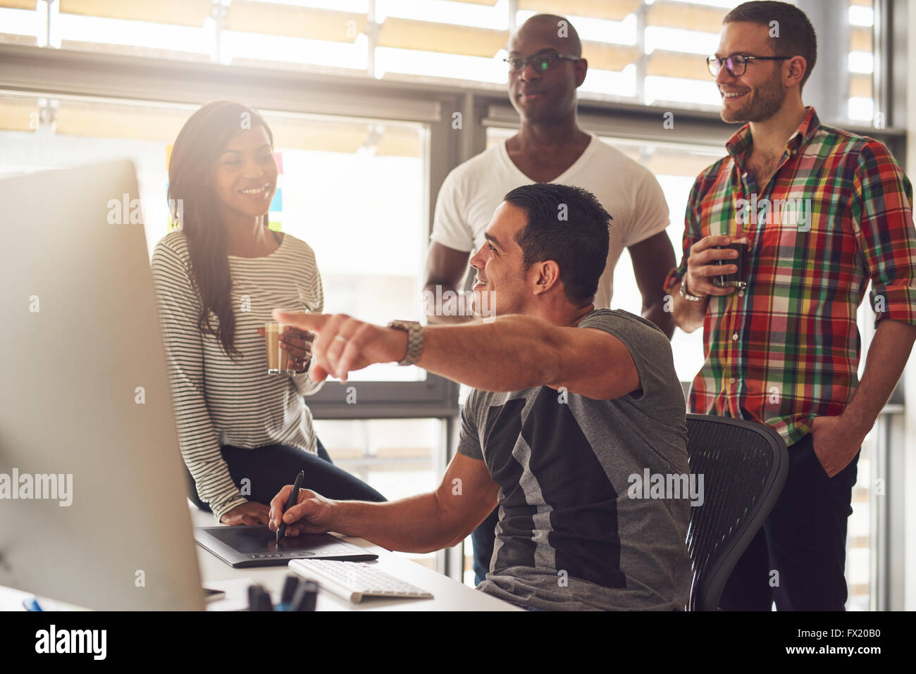 Man with stylus and tablet showing something on his computer to a group of three male and female casually dressed - Stock Image