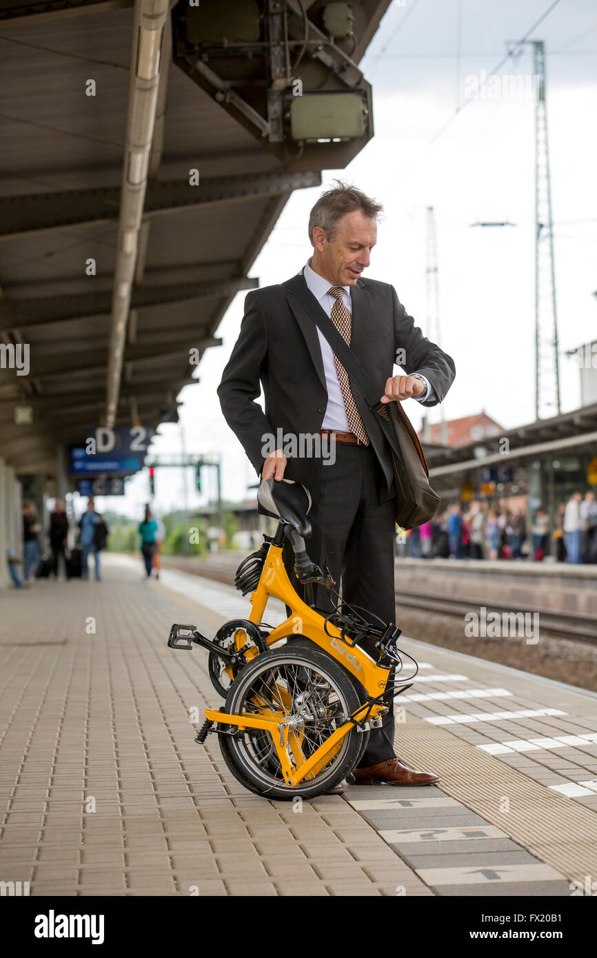 Businessman with folding bike on the platform looks at his watch - Stock Image