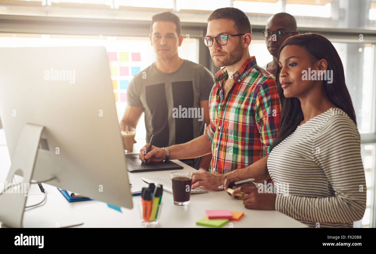 Group of four Black, Caucasian and Hispanic adult entrepreneurs wearing casual clothing while standing around computer - Stock Image