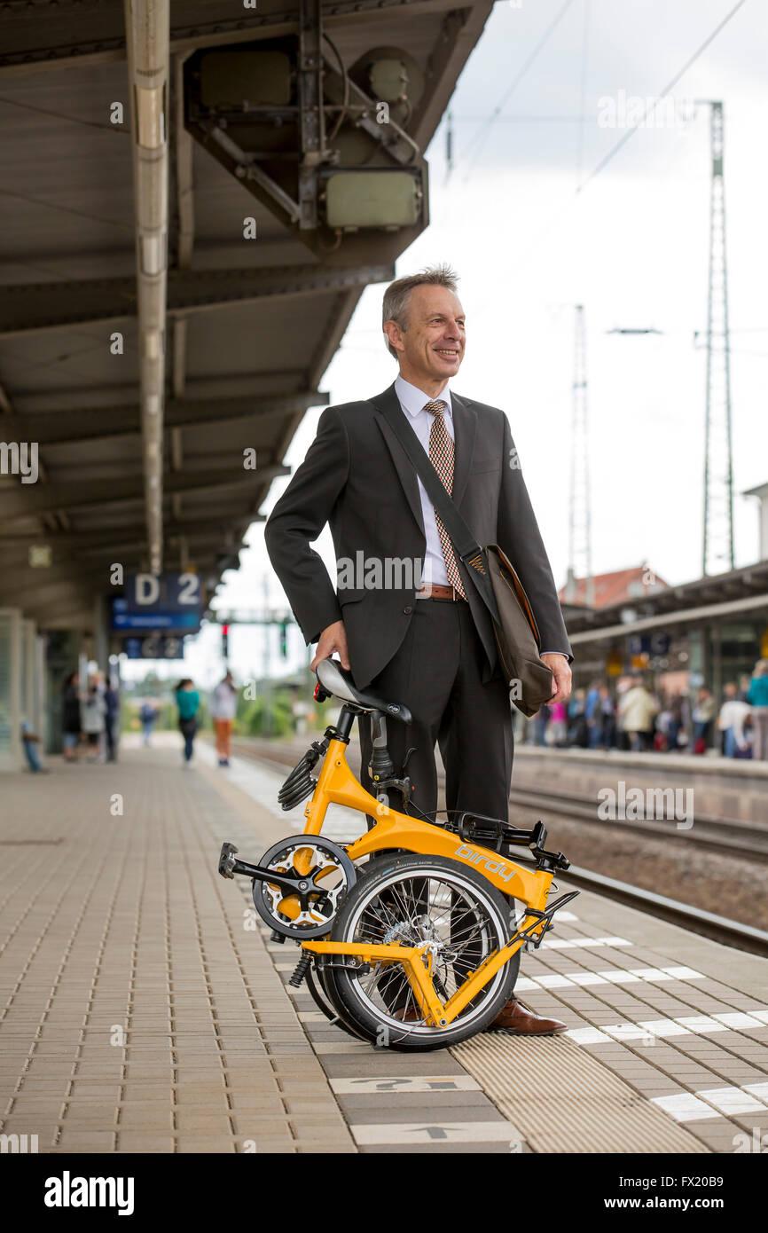 Businessman with folding bike on railway platform - Stock Image