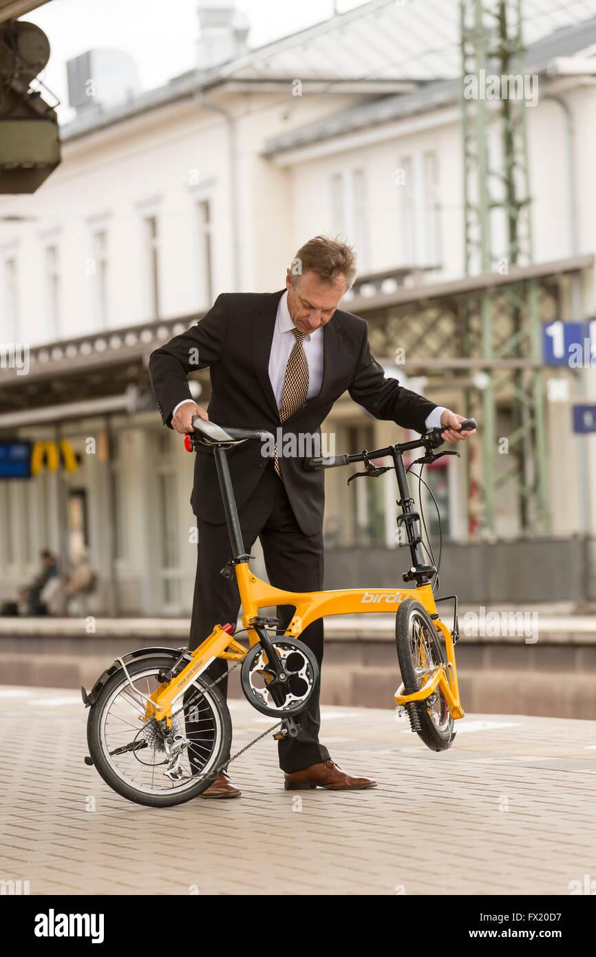 Businessman folding his folding bike on a train platform Stock Photo