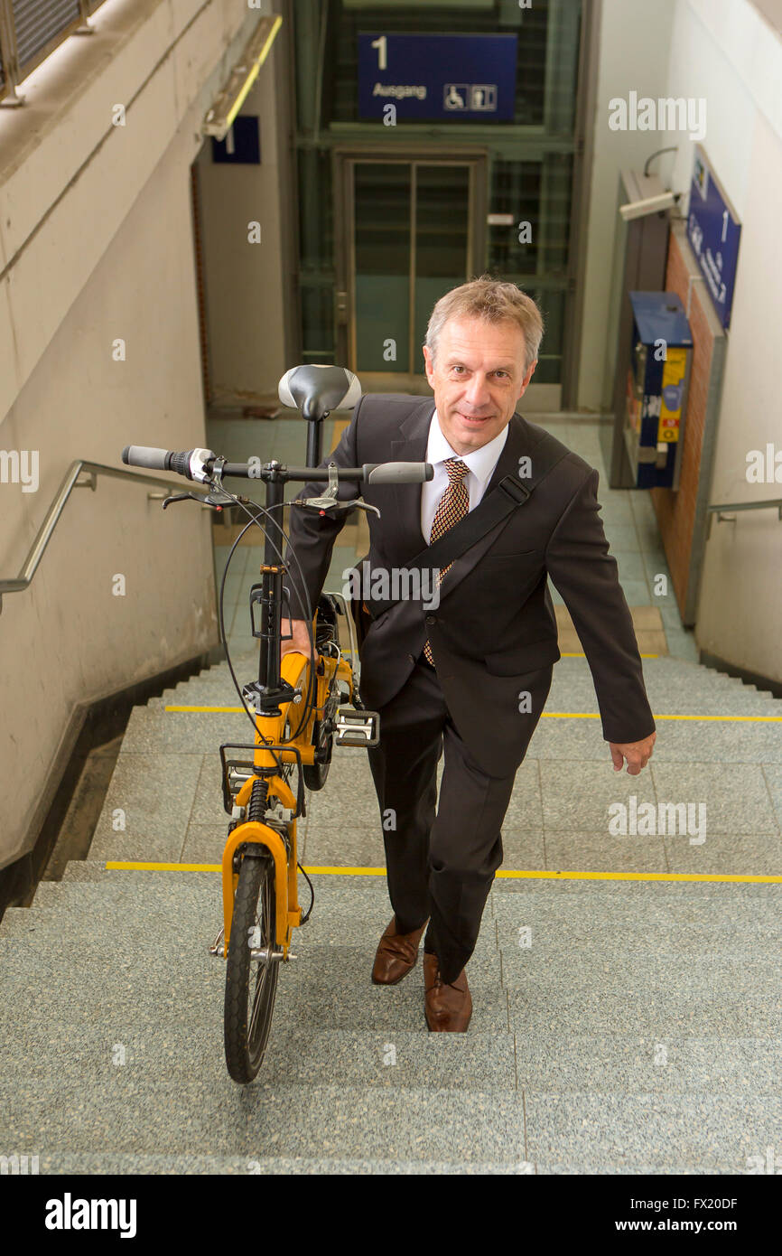 Businessman with folding bike goes up the stair in the railway station - Stock Image