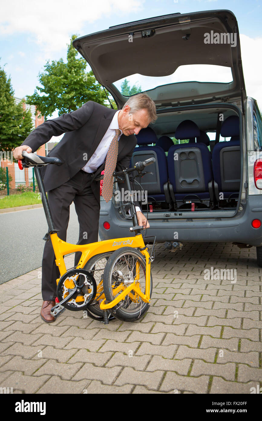 Business man grabs his folding bike in the car trunk - Stock Image