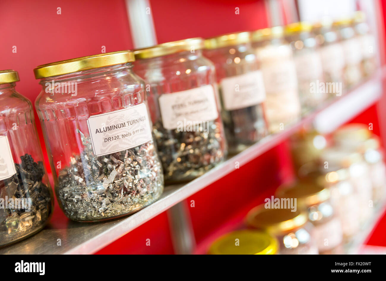 Aluminum turnings in a glass jar among other jars full of different metal turnings result of metal cutting. - Stock Image