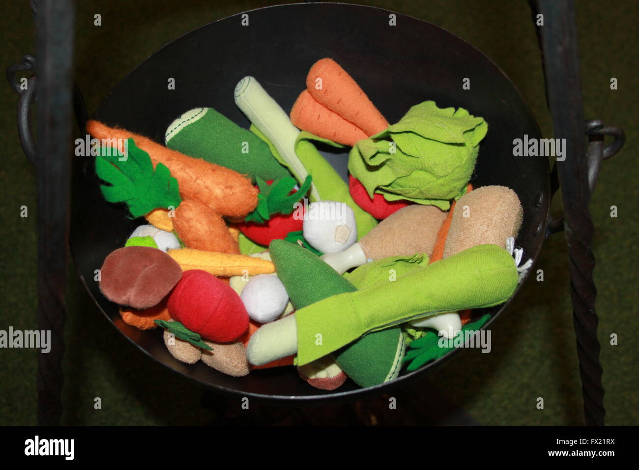 Black soup pot, pan or cauldron of colorful fabric pretend broth or soup chicken and vegetables - Stock Image