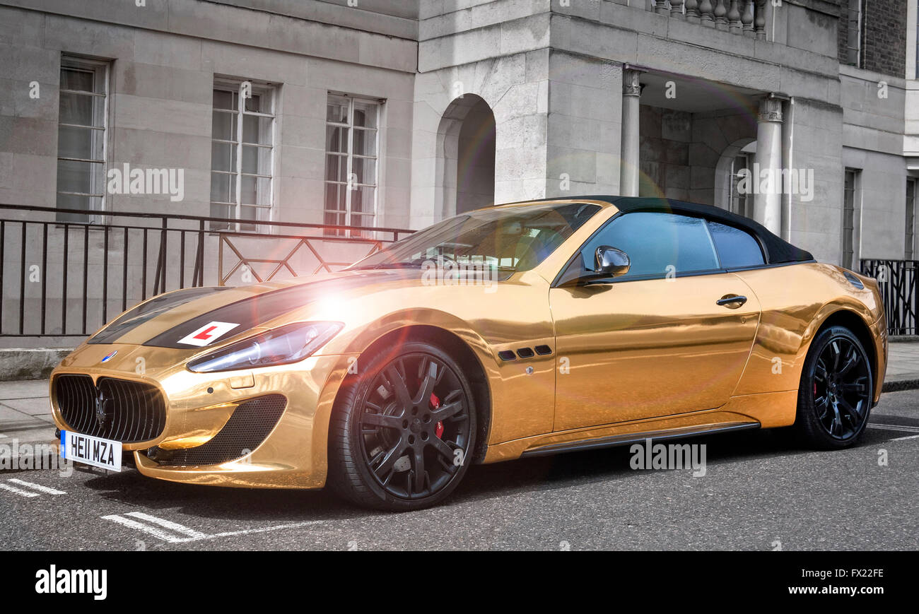 Gold plated Maserati Grand Turismo Convertible MC with a learner drivers L plate attached,parked in a street in - Stock Image