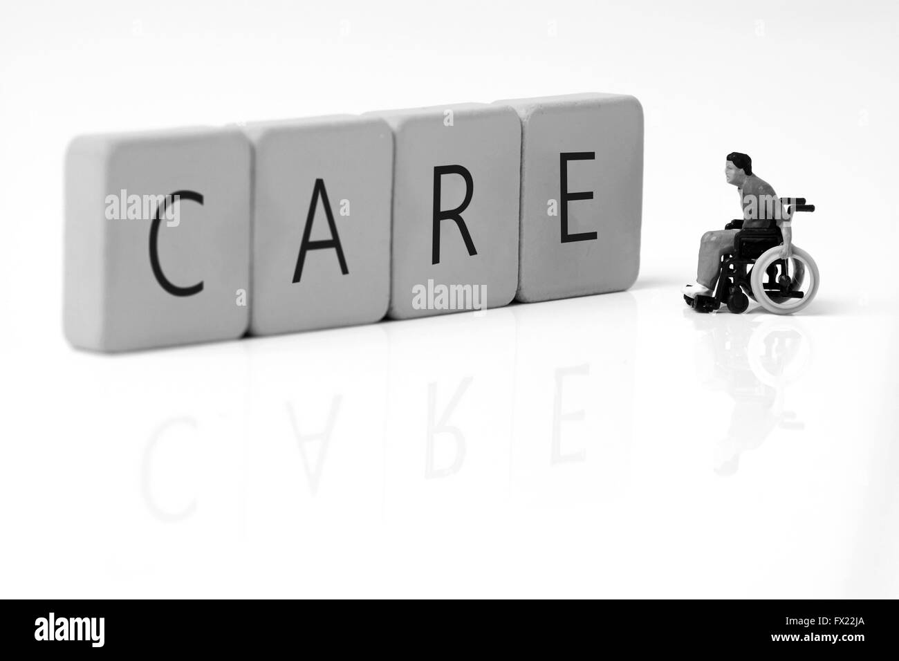Miniature model man wheelchair tiles care - Stock Image