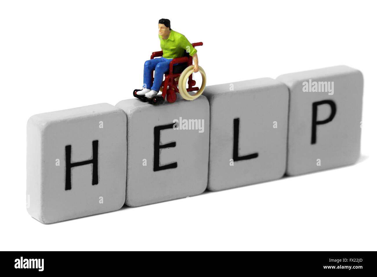 Miniature model man wheelchair help - Stock Image
