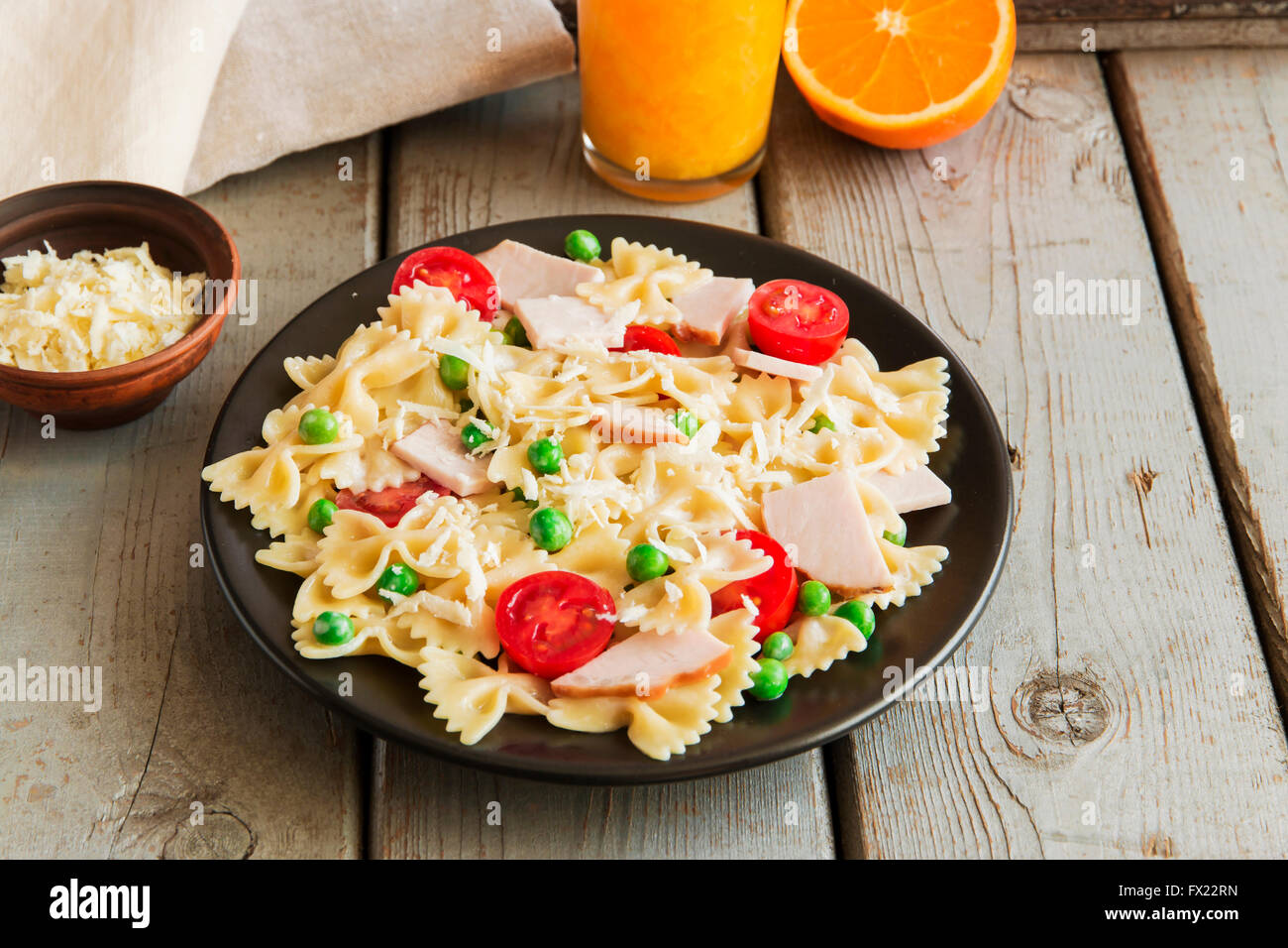 Pasta with ham and green peas tomato cheese - Stock Image