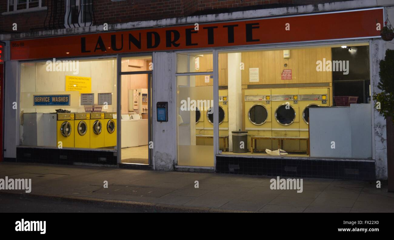 An empty lonely laundrette at dusk on an urban street - Stock Image