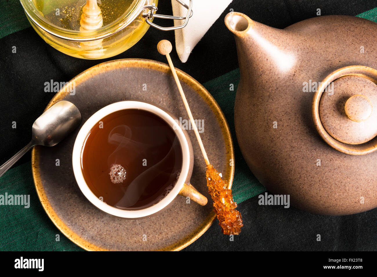 A cup of hot tea on a table with teapot and honey. Shot from above - Stock Image
