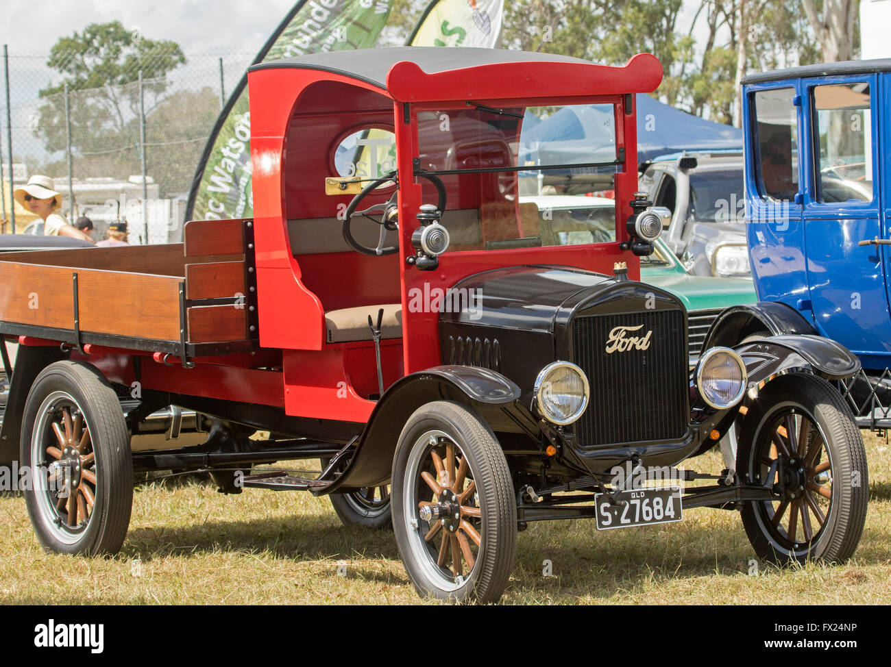 Perfectly restored vintage Ford truck / delivery vehicle with gleaming red doorless cab and wooden tray Stock Photo