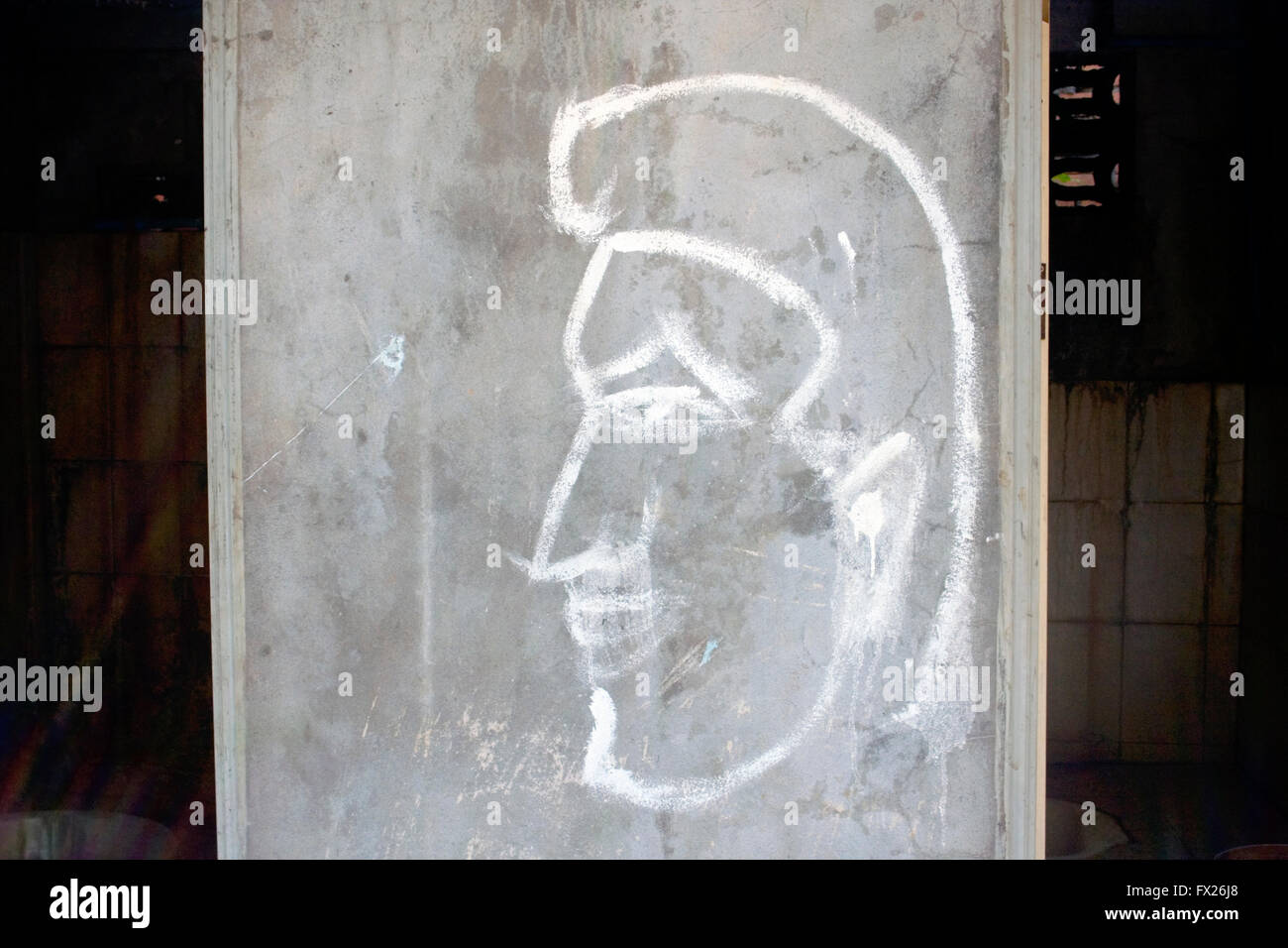 Graffiti of a man is drawn on a wall marking a bathroom on the grounds of a Buddhist temple in Tboung Khmum Province, Stock Photo