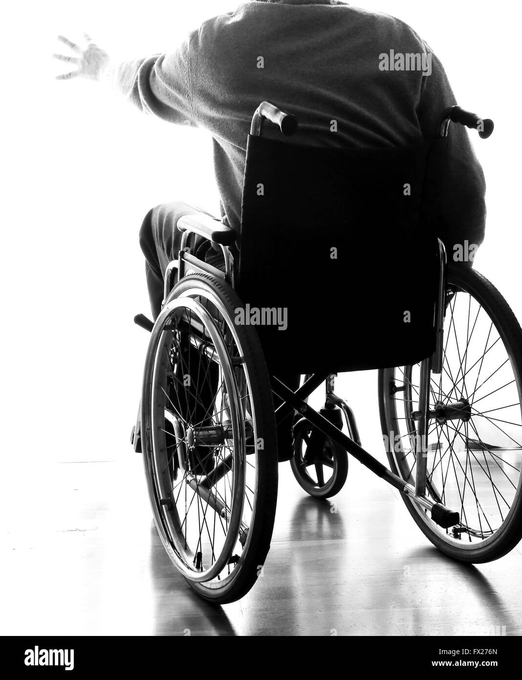 disabled elderly sitting in a wheelchair in the his room - Stock Image