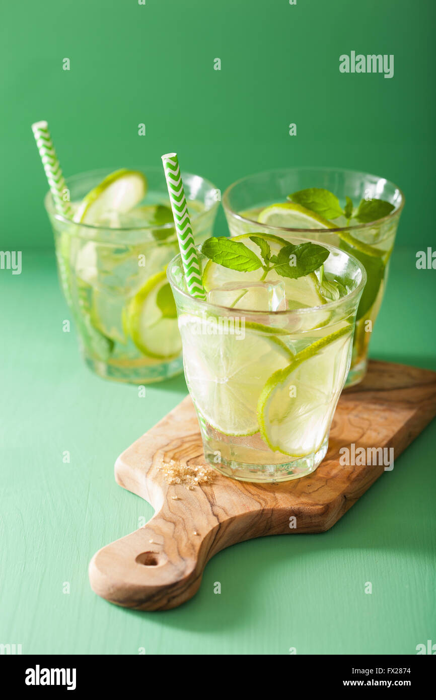 mojito cocktail and ingredients over green background - Stock Image