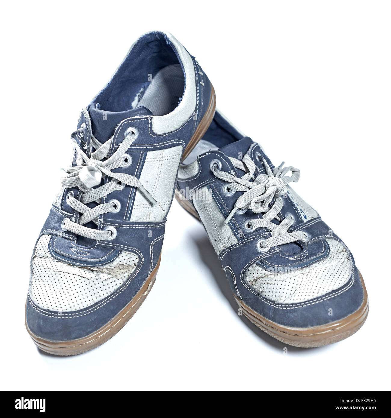 Old worn out sneakers isolated on white - Stock Image
