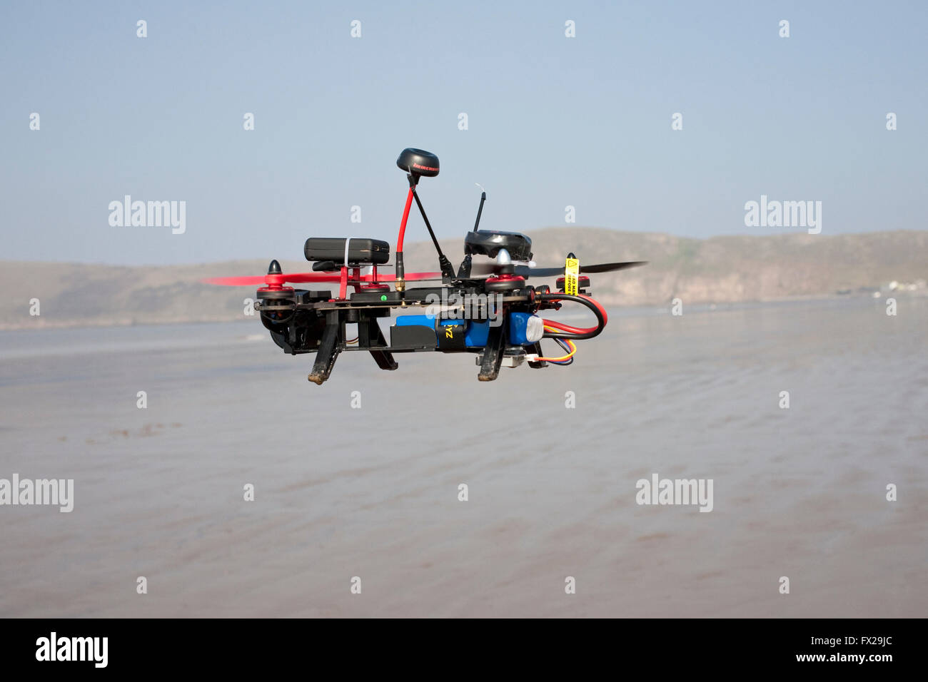 radio controlled drone being flown on an empty beach - Stock Image