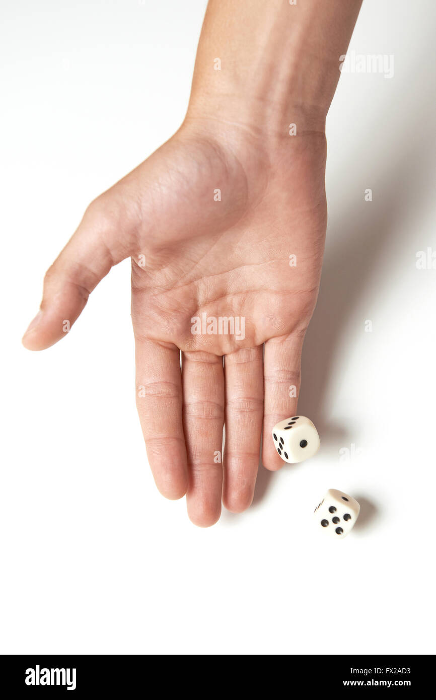 Hand throwing two dices on a white table Stock Photo