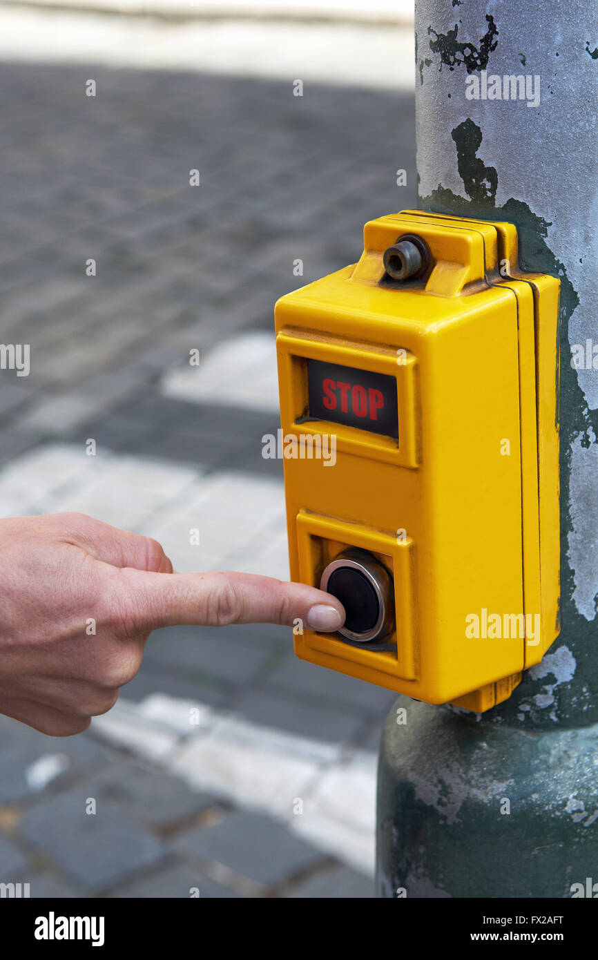 Person pushing the button on a crosswalk device - Stock Image