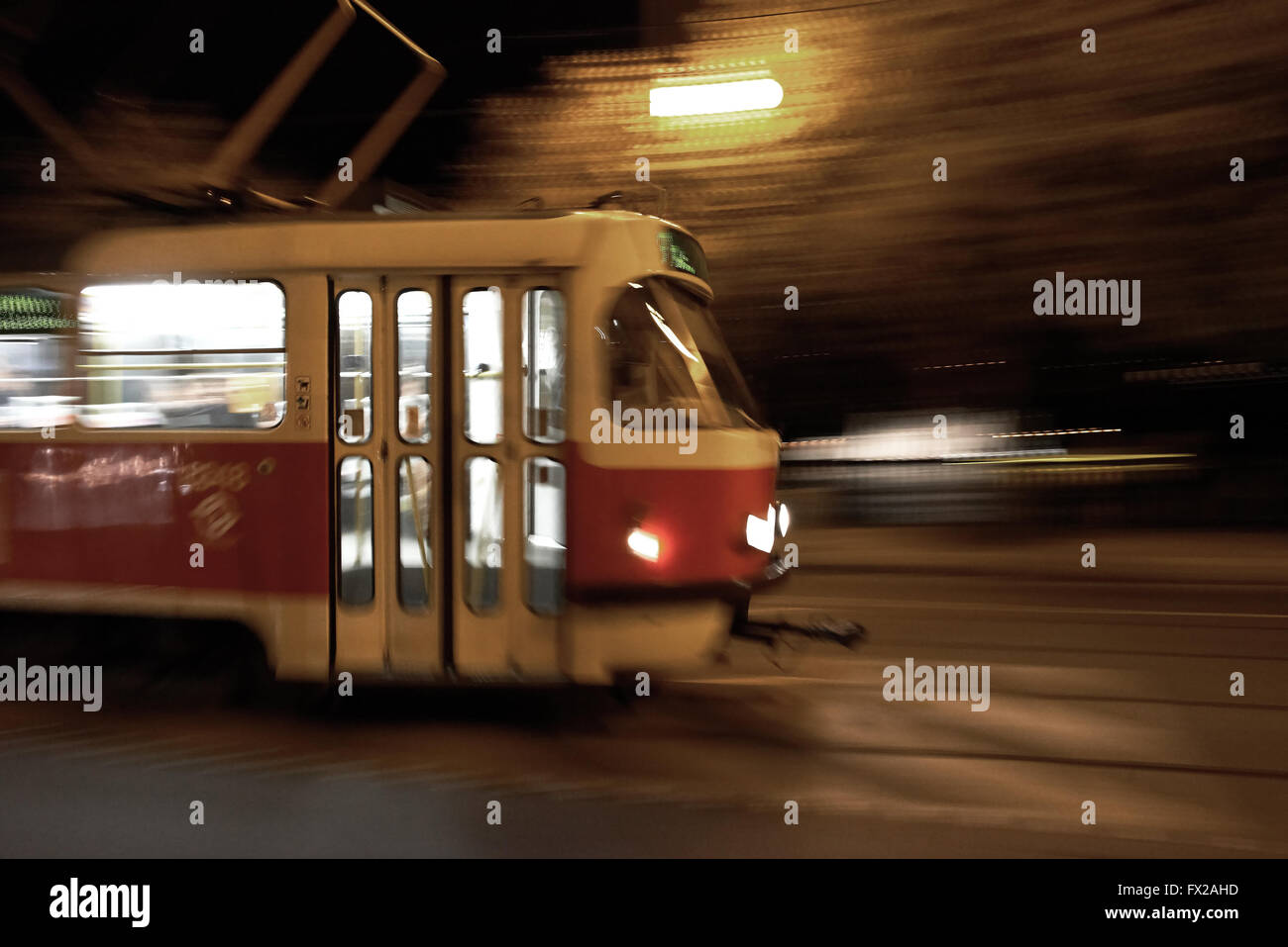 Red and white Tram moving thru the city with motion blur - Stock Image