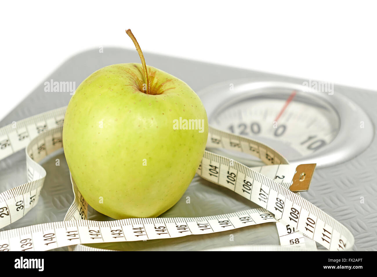 An apple, messure tape and a weight scale Illustrating a healthy lifestyle - Stock Image
