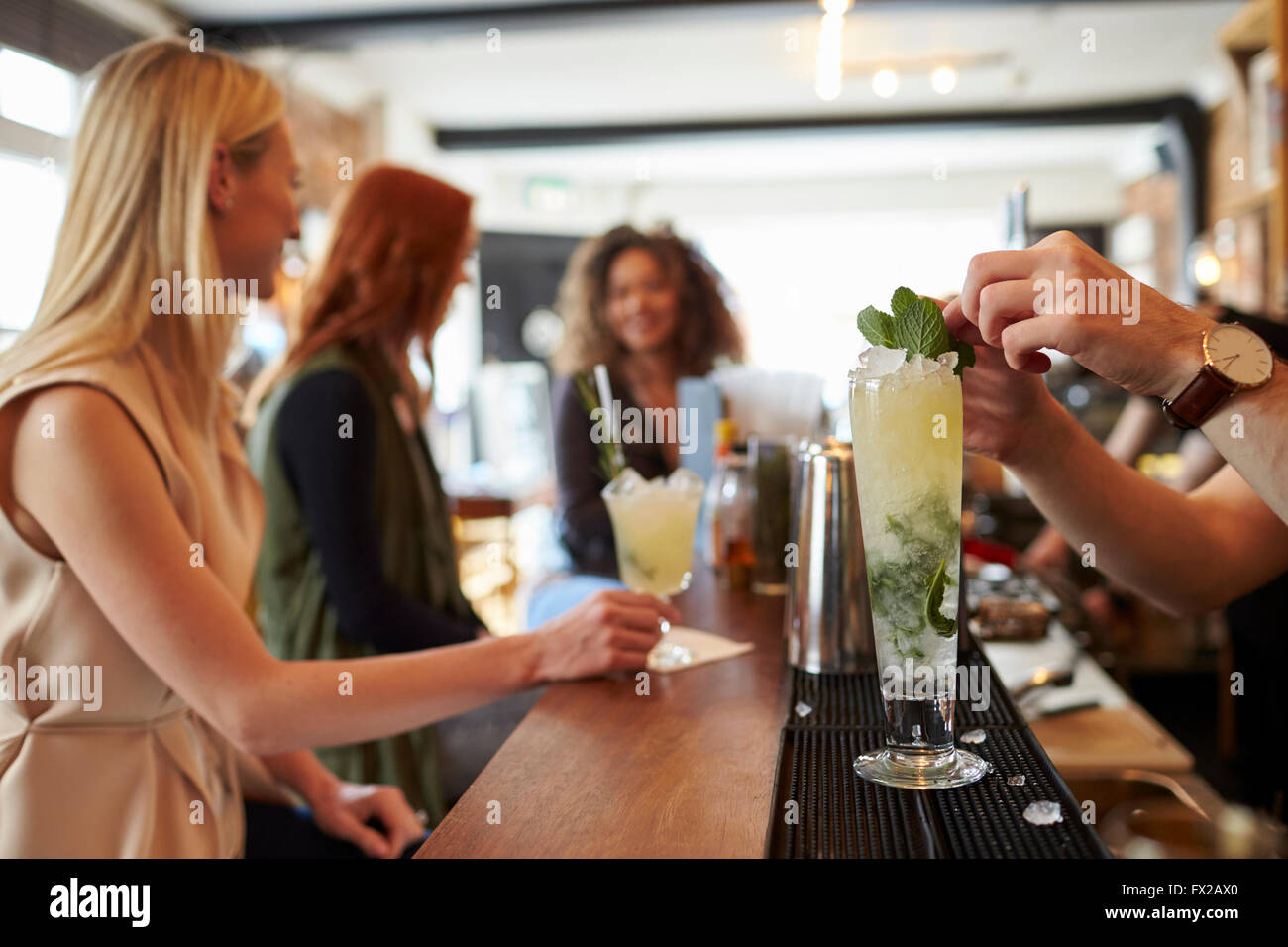 Barman Making Mojito Cocktail With Customers In Background - Stock Image