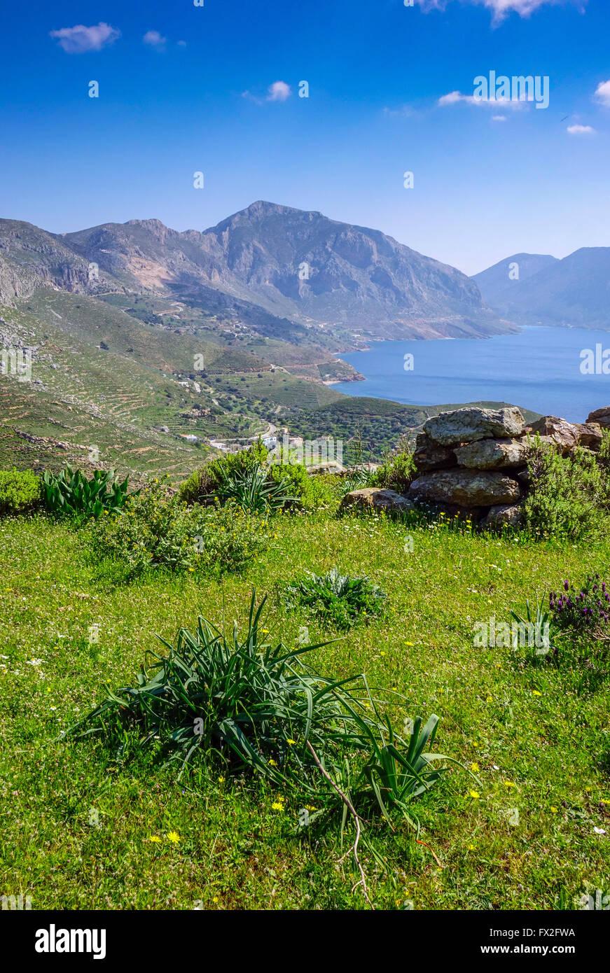 Blue sea spring greenery and mountains at Emborios Bay Kalymnos, Greece - Stock Image