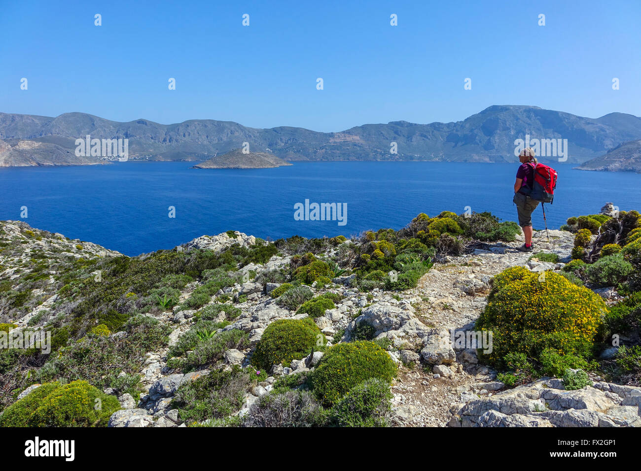 Female walker with red rucksack, Blue sea and mountains at Emborios Bay Kalymnos, Greece - Stock Image