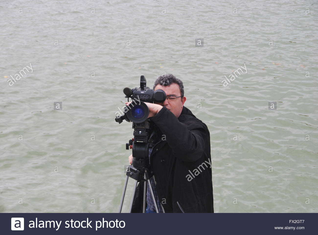 Professional cameraman with video camera in shooting process. Digital media - Stock Image