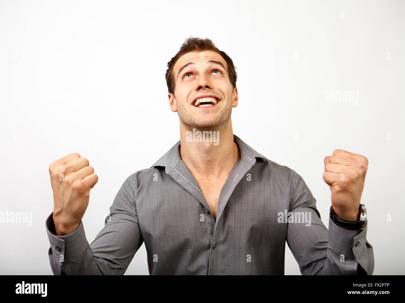 Excited male winner  expressing victory and success. Successful business man isolated on grey - Stock Image