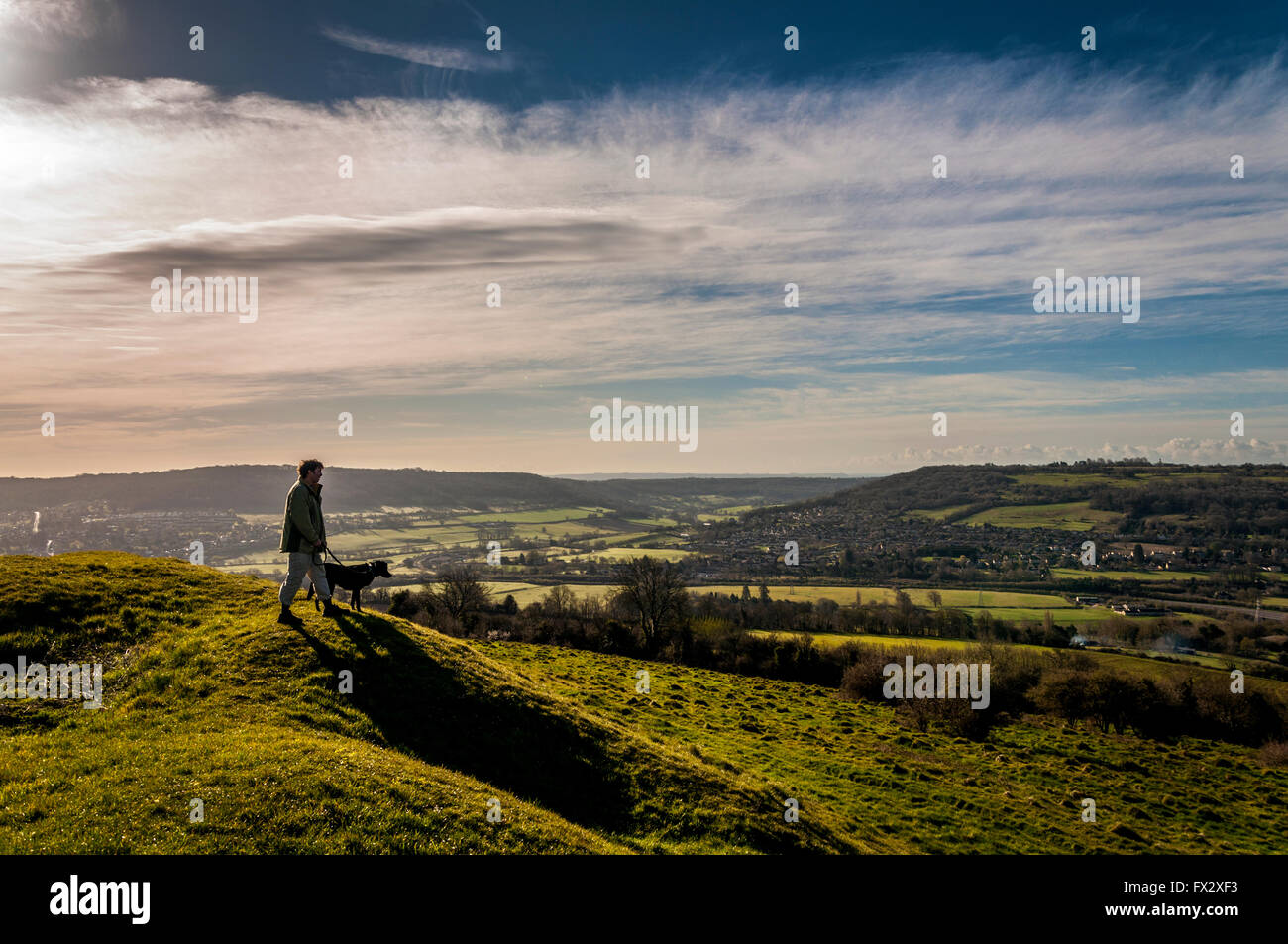 Little Solsbury Hill, Batheaston, Somerset, UK . A dog walker  admires the view from the top of the old Iron Age Stock Photo