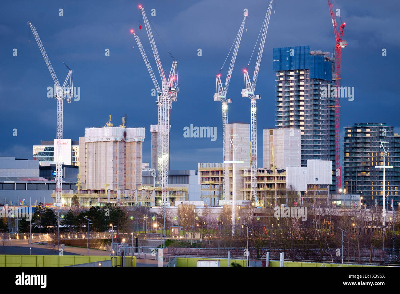 New skyscrapers in the International Quarter of the Queen Elizabeth Olympic Park stand out against a stormy twilight - Stock Image