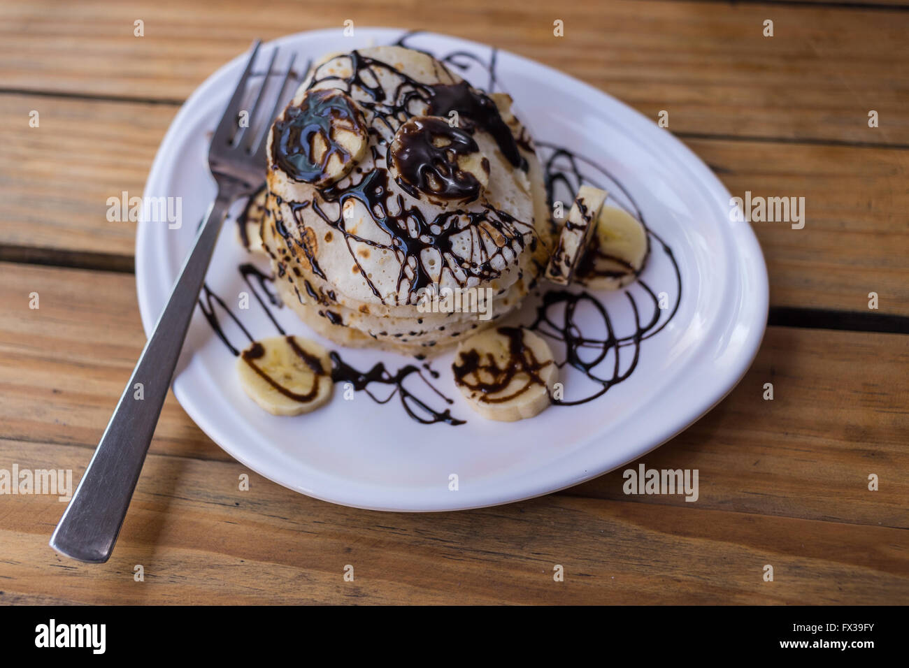 Stack of Pancakes in a restaurant with banana and chocolate sauce on top. Stock Photo