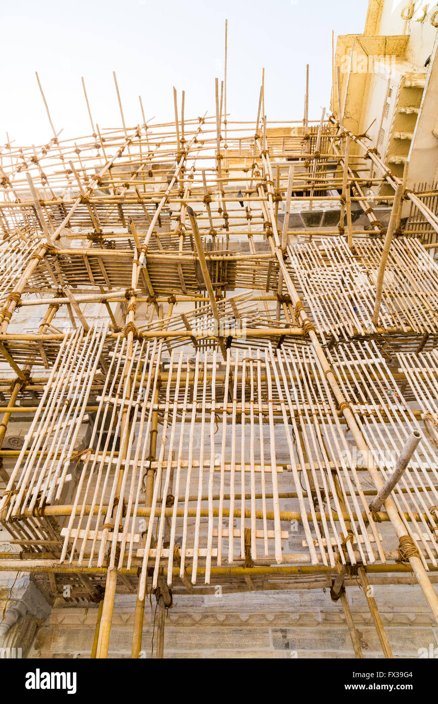 Scaffolding at the side of a wall in India made from Bamboo - Stock Image