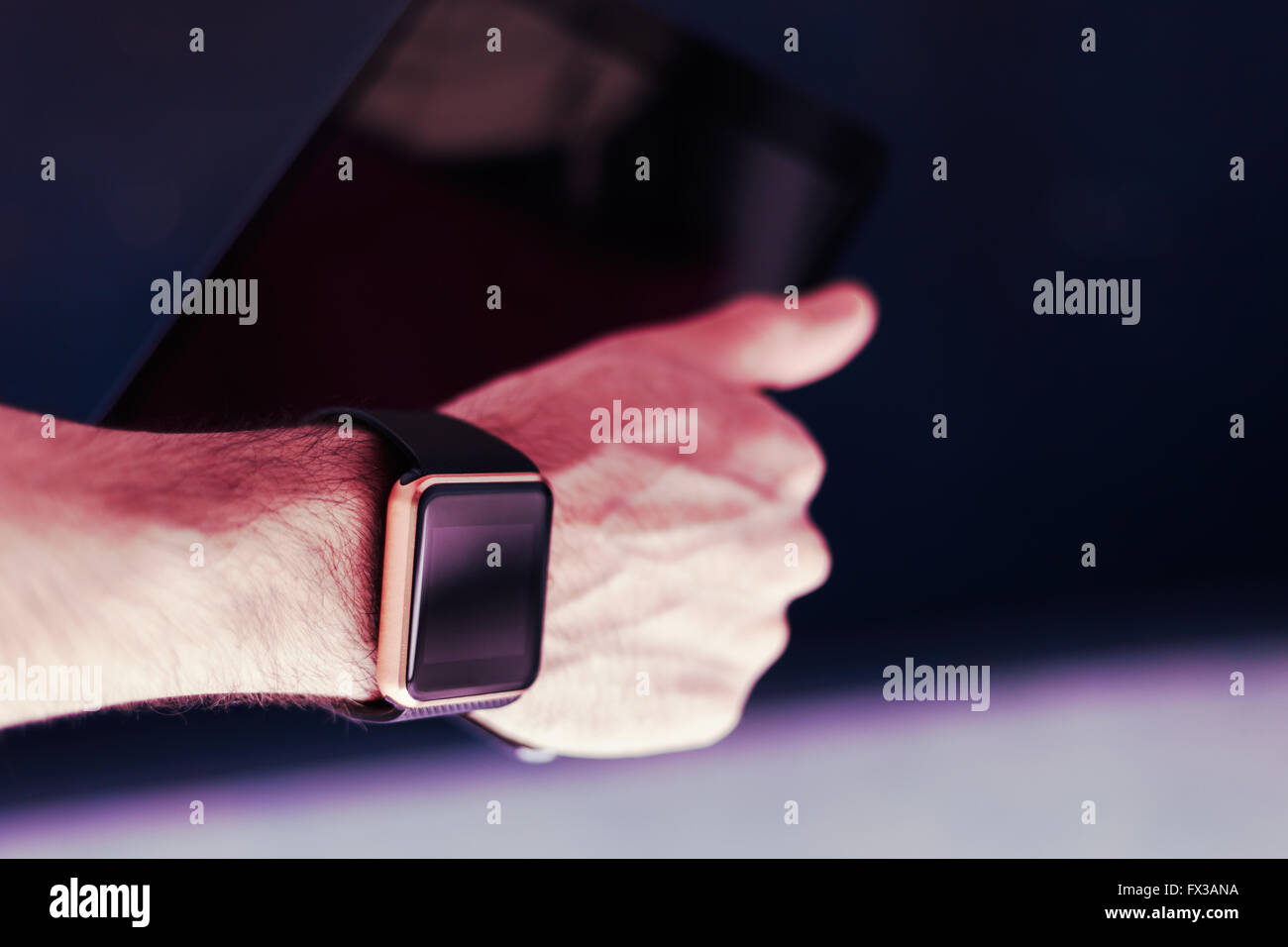 Male hand with two devices on it - trandy smart watch and tablet pc. This person is always connected to internet - Stock Image