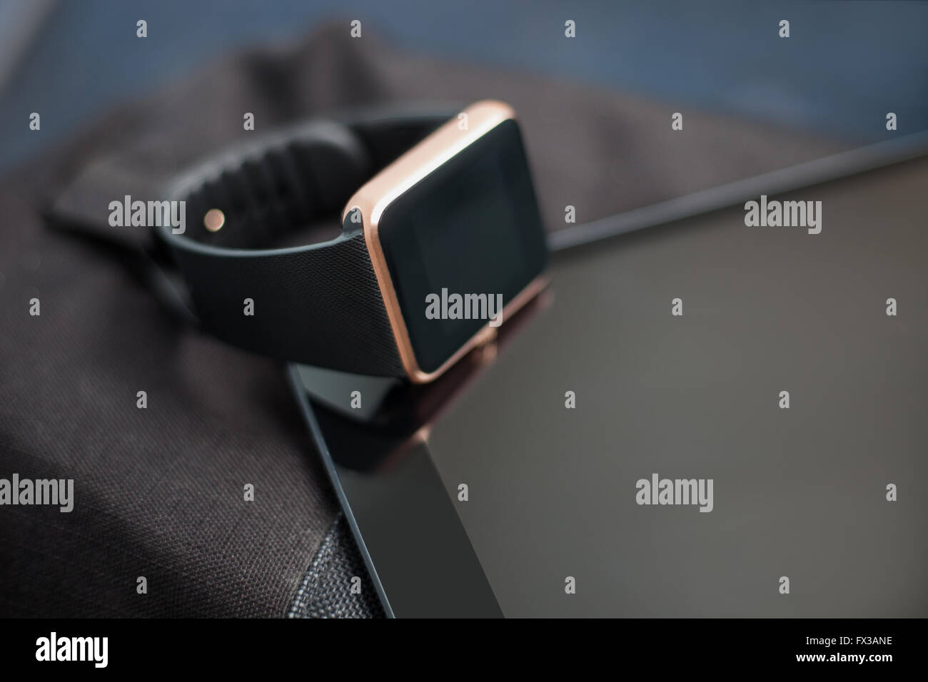Modern digital accessory - fashionable smart wrist watch on talbet pc and travel bag. This gadgets let you always - Stock Image