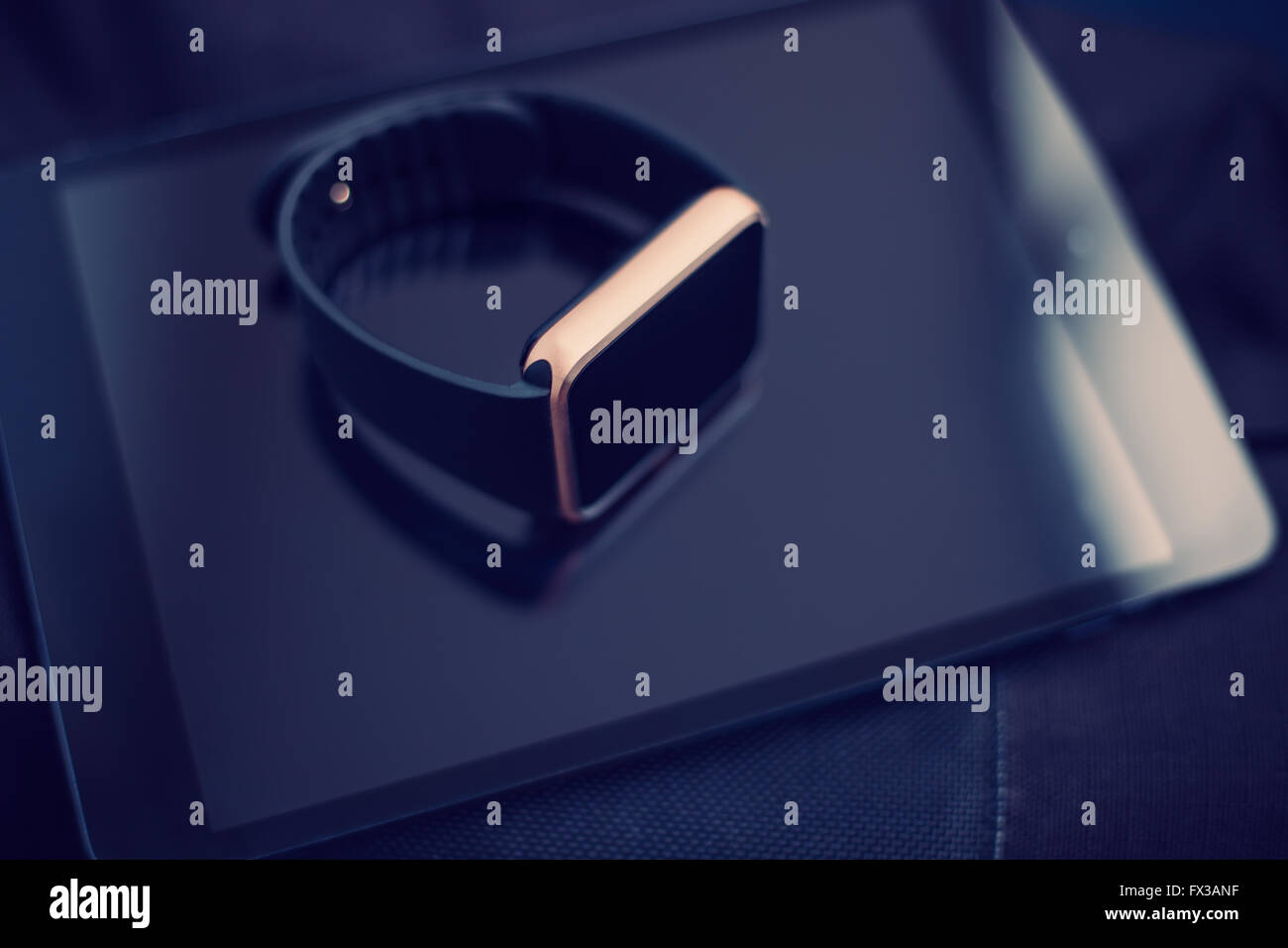 Smart wrist watch laying on a talbet pc. This gadgets will let you always stay connected to the social media and - Stock Image