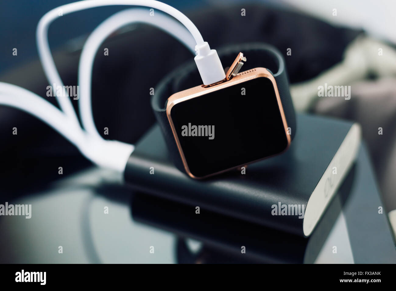 Smart wrist watch charging from a travel powerbank charger. Travel and stay connected to the media networks form - Stock Image