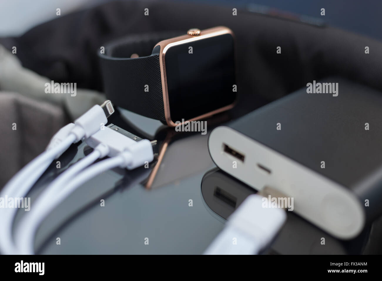 Travel charger and smart wrist watch and cable management for charge. This portable devices will let you stay connected - Stock Image