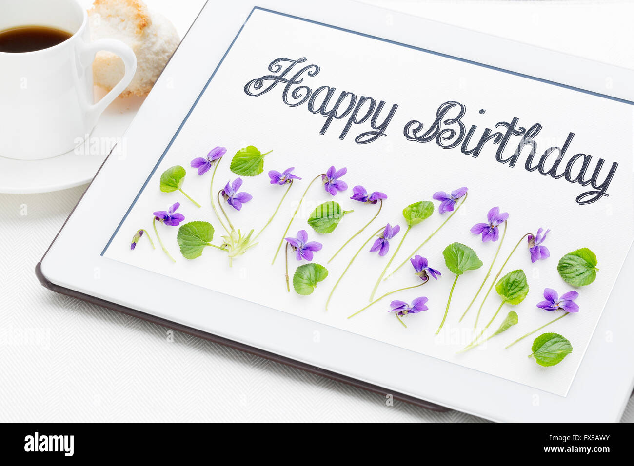 Happy birthday greeting card handwriting with viola flowers and happy birthday greeting card handwriting with viola flowers and leaves on digital tablet with a cup of coffee m4hsunfo