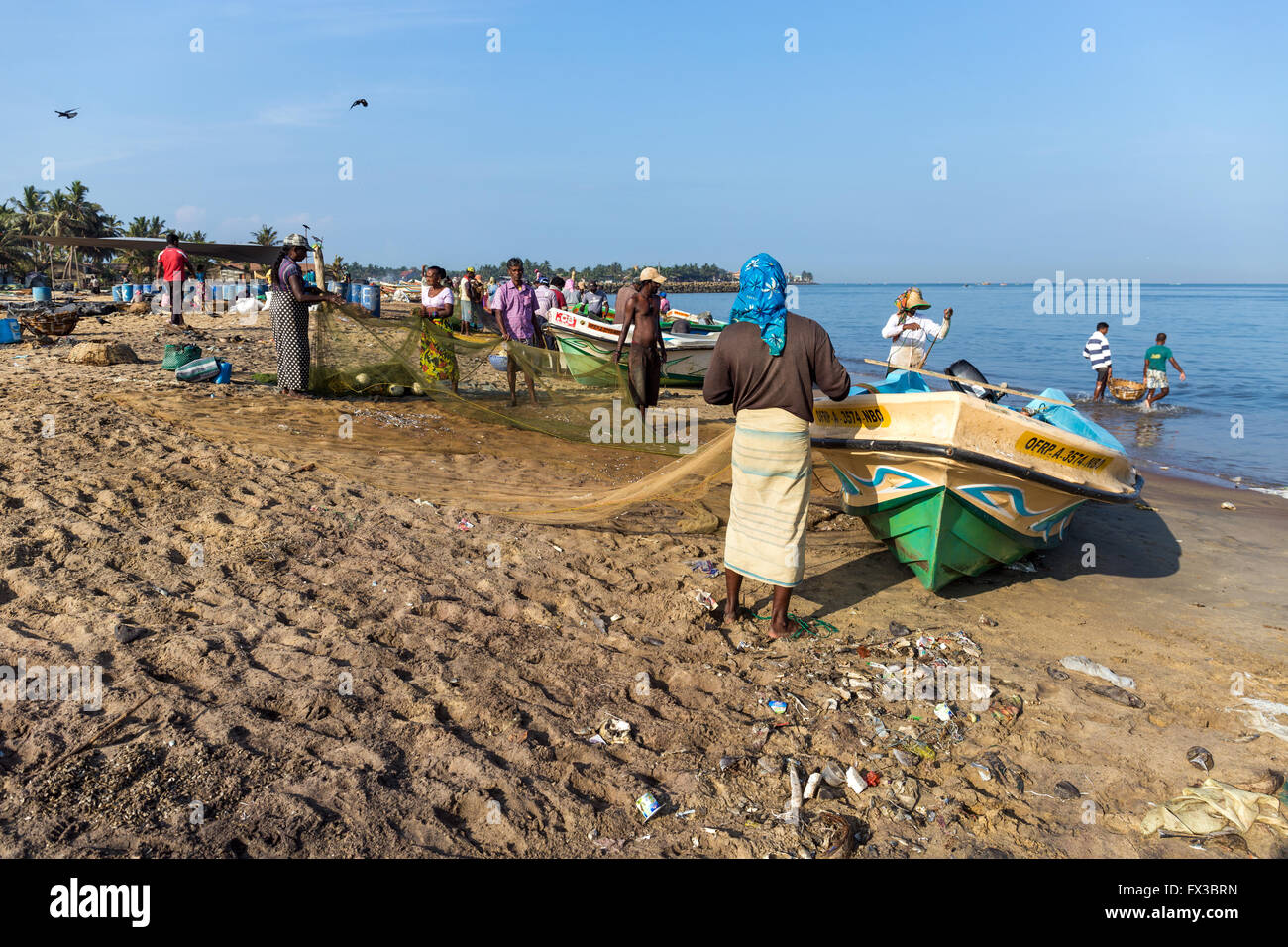 People repairing fishing nets amidst their colorful fishing boats at Negombo Beach, Sri Lanka Stock Photo