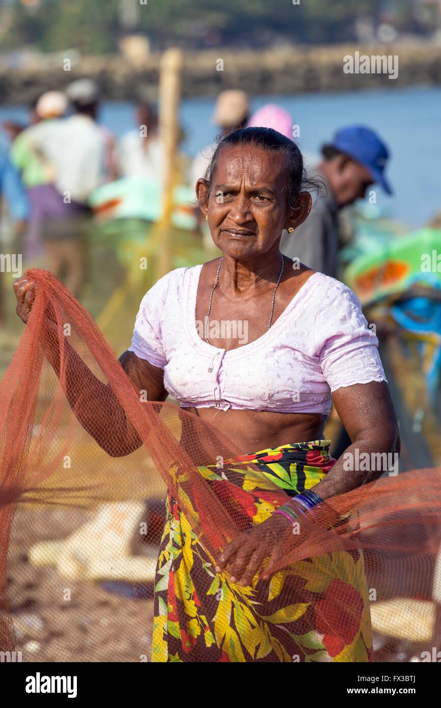 People repairing fishing nets amidst their colorful fishing boats at Negombo Beach, Sri Lanka Stock Photo