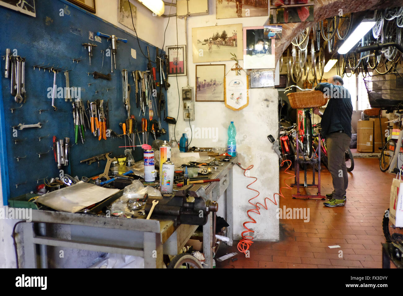 Interior of the cycle workshop of Poli in Lucca, Tuscany. Italy. Showing work bench and tools, mechanic and various - Stock Image