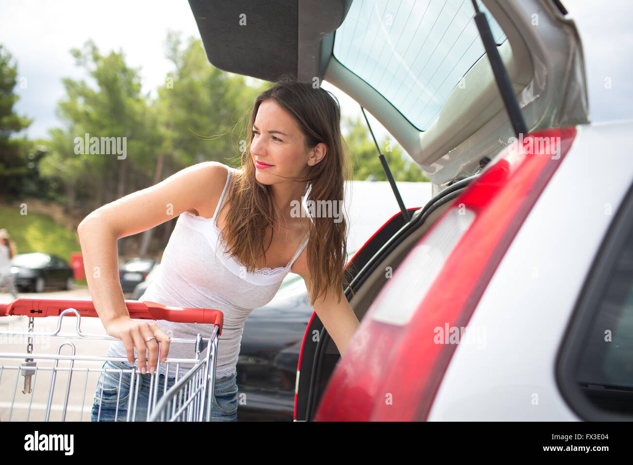 Beautiful young woman shopping in a grocery store/supermarket, putting the groceries she bought in her car (color - Stock Image