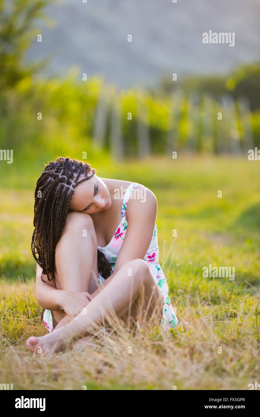 Pretty countrygirl is sad outdoors sitting seated cross legged sits upset discarded field stressed stress apparently - Stock Image